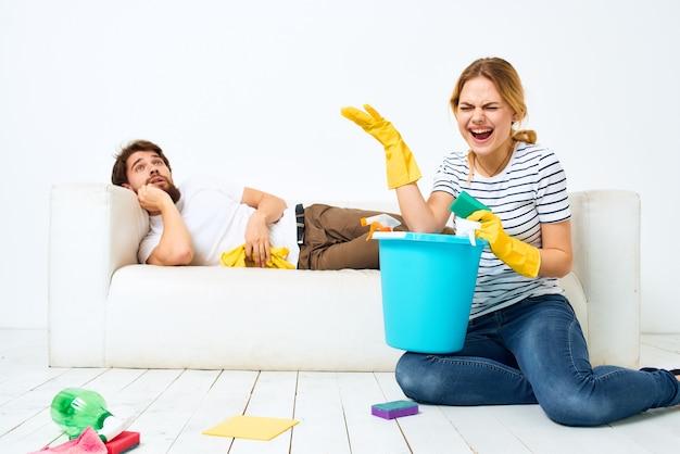 Jeune couple avec des gants en caoutchouc et des produits de nettoyage dans leur appartement