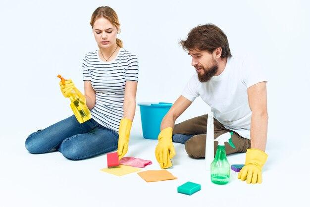 Jeune couple avec des gants en caoutchouc et des produits de nettoyage