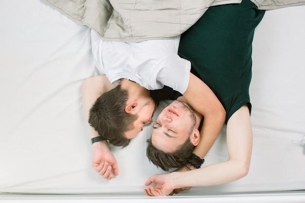 Jeune couple gay allongé sur le lit, vue de dessus. la saint-valentin. deux mecs sexy sur le lit.