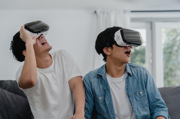 Jeune couple gay asiatique utilisant une technologie amusante à la maison, mec amant de l'asie lgbtq + se sentant heureux de s'amuser et de la réalité virtuelle, vr jouant à des jeux ensemble tout en restant allongé sur un canapé dans le salon à la maison.