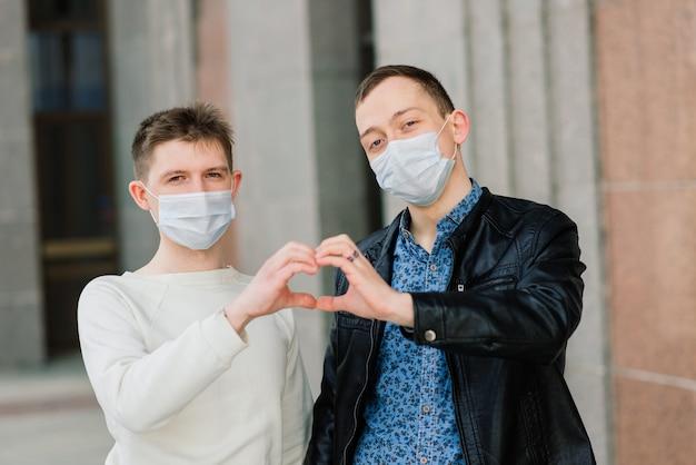 Jeune couple gay portant un masque médical étreignant la ville.