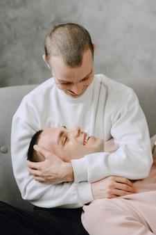 Jeune couple gay romantique passant la journée à se câliner et à se détendre sur le canapé