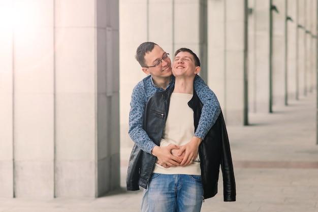 Jeune couple gay souriant heureux et étreignant à la ville