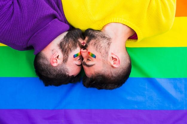 Jeune couple de gays s'embrasser sur le drapeau arc-en-ciel
