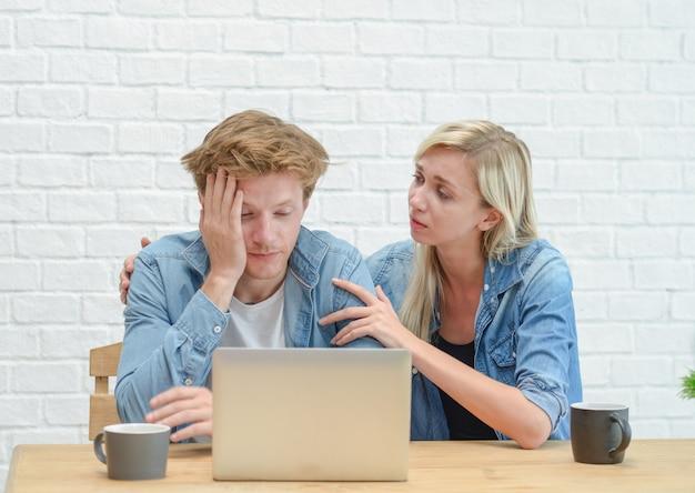 Jeune couple gérant son budget familial sérieux, assis sur la salle blanche.