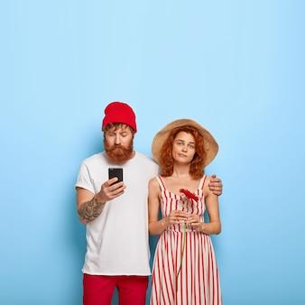 Jeune couple de gingembre élégant posant ensemble