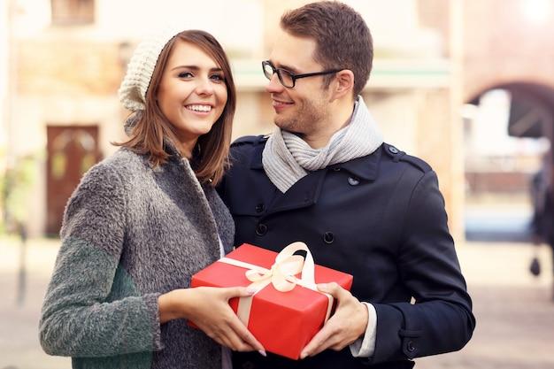 Jeune couple avec grand cadeau dans la ville
