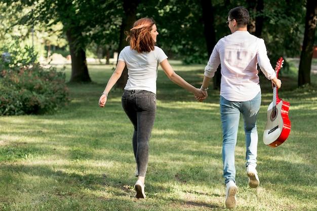 Jeune couple avec une guitare s'éloignant