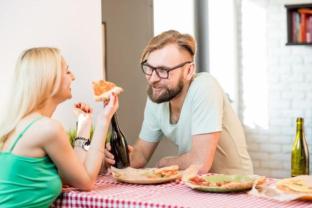 Jeune couple habillé avec désinvolture en train de déjeuner avec pizza et bière à la maison