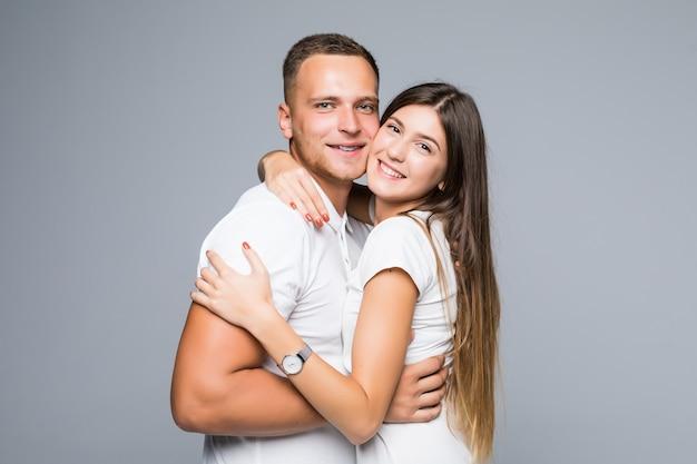 Jeune couple habillé en t-shirts blancs ayant des câlins amicaux romantiques isolés