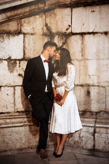 Jeune couple en habits élégants s'embrassant dans la rue
