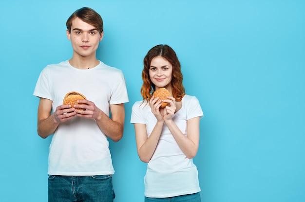 Jeune couple avec des hamburgers dans leurs mains fast food snack malbouffe