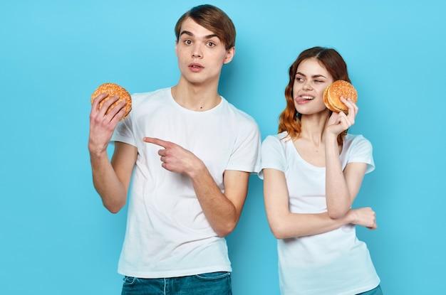 Jeune couple hamburgers dans les mains snack style de vie fond bleu. photo de haute qualité