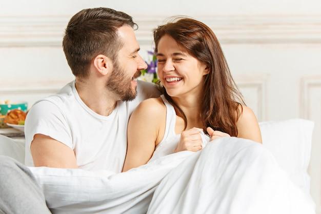 Jeune couple hétérosexuel adulte allongé sur le lit dans la chambre