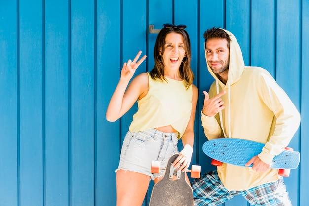 Jeune couple heureux d'amis posant avec des planches à roulettes