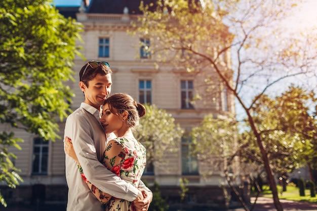 Jeune couple heureux en amour étreignant à l'extérieur.