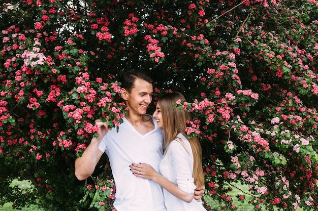 Jeune couple heureux amoureux à l'extérieur. aimer l'homme et la femme lors d'une promenade dans un parc fleuri au printemps