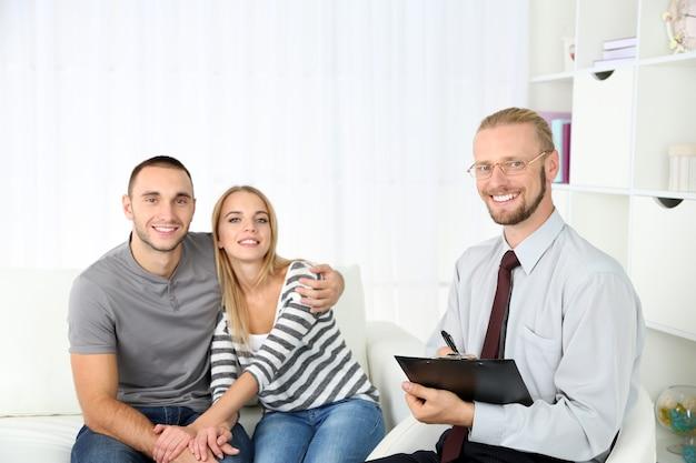 Jeune couple heureux après une séance de thérapie avec un psychologue familial