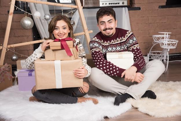 Jeune couple heureux assis avec des cadeaux de noël près des boules d'argent festives.