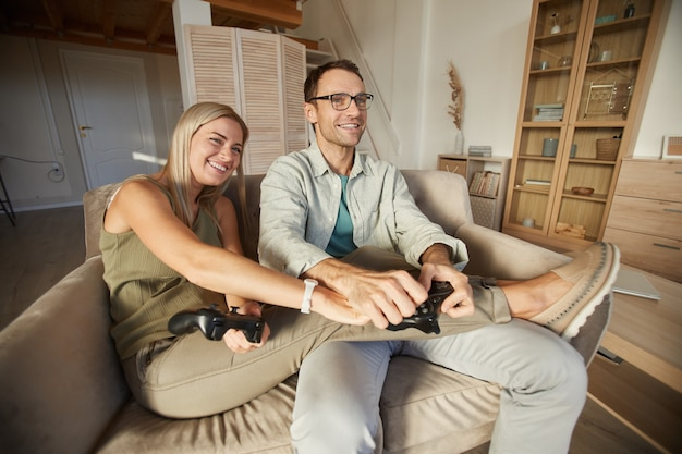Jeune couple heureux assis sur un canapé et jouer à des jeux informatiques ensemble à l'aide de joysticks à la maison