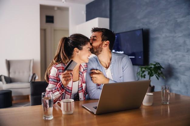 Jeune couple heureux assis à la maison et utilisant un ordinateur portable pour faire des achats en ligne. l'homme embrasse la femme tandis que la femme tient la carte de crédit.