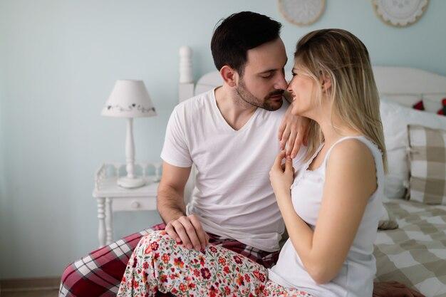 Jeune couple heureux attrayant ayant un moment romantique au lit