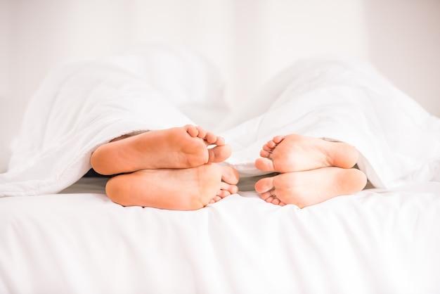 Jeune couple heureux au lit à la maison.