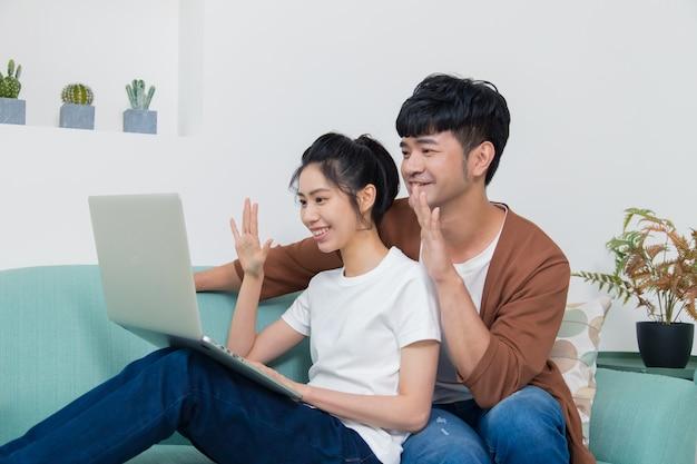 Jeune couple heureux ayant un appel vidéo familial.