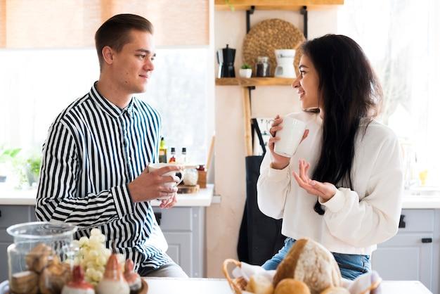 Jeune couple heureux, boire des boissons et parler