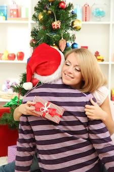 Jeune couple heureux avec des cadeaux assis près de l'arbre de noël à la maison