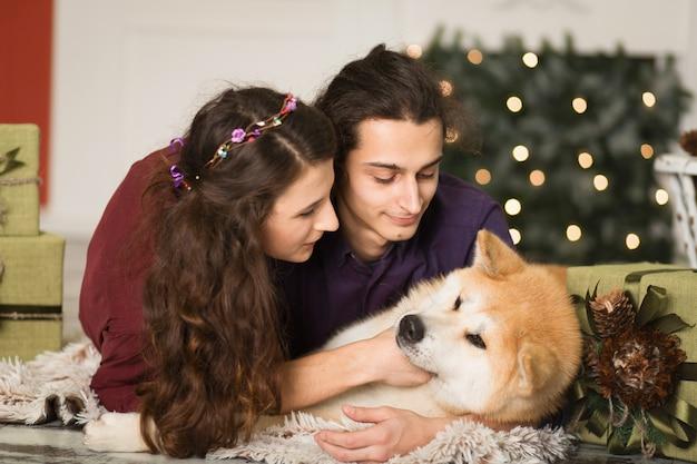 Jeune couple heureux câlins adorable chien akita inu avec sur le sol pour les vacances de noël à la maison.