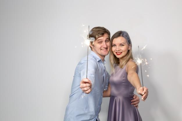 Jeune couple heureux avec des cierges magiques sur mur blanc