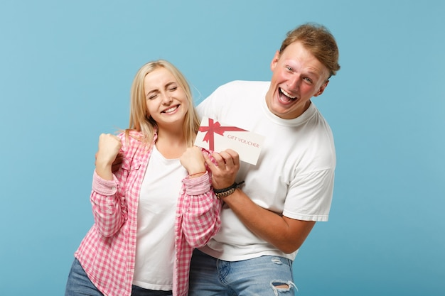 Jeune couple heureux deux ami gars et femme en t-shirts vides roses blancs posant