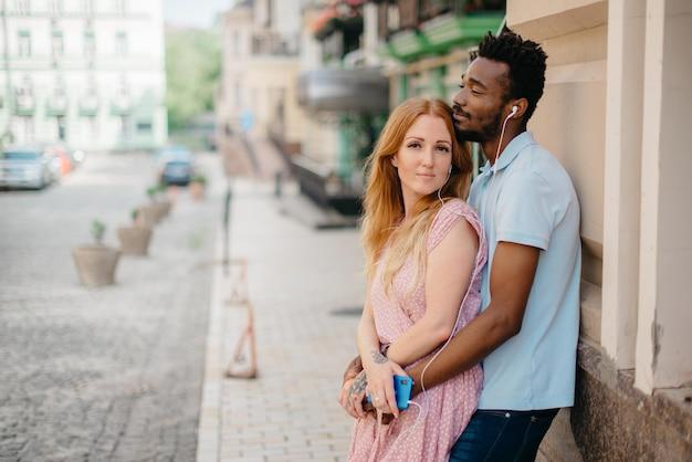 Jeune couple heureux, écouter de la musique avec des écouteurs dans une rue de la ville par une journée ensoleillée