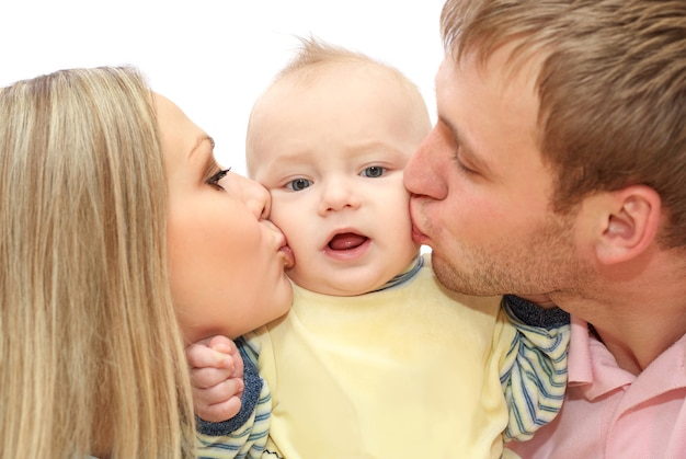 Un jeune couple heureux embrasse le bébé