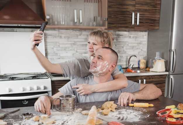 Un jeune couple heureux enduit de farine prend un selfie dans la cuisine. mari et femme heureux et aimant