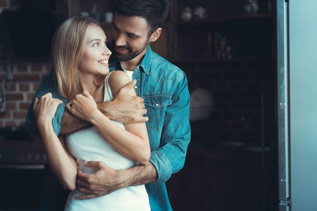 Jeune couple heureux étreignant et se regardant à l'intérieur d'une nouvelle cuisine, bonheur dans une nouvelle maison.
