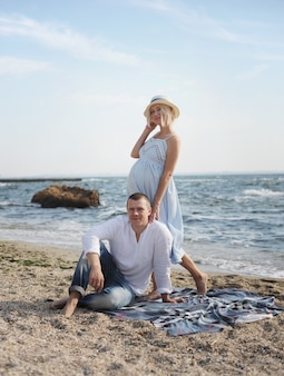 Jeune couple heureux futurs parents posant près de l'océan