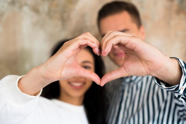 Jeune couple heureux gesticulant coeur avec les mains