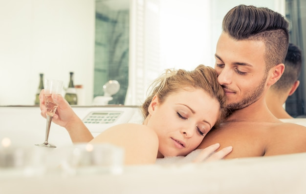 Jeune couple heureux heureux bénéficiant d'un bain chaud dans le jacuzi