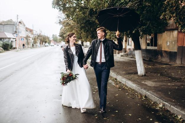 Jeune couple heureux marche dans une rue de la ville après la pluie. portrait de gros plan d'un homme et d'une femme avec un parapluie. couple d'amoureux souriant à l'extérieur. un homme marche dans la rue et agite un parapluie