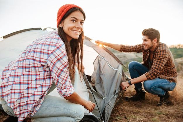 Jeune couple heureux la mise en place d'une tente à l'extérieur
