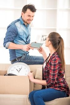 Jeune couple heureux organisant l'appartement.