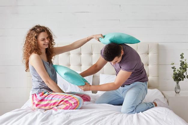 Un jeune couple heureux passe du temps libre à la maison dans la chambre, fait la bataille d'oreillers, a des expressions positives, est de bonne humeur après un sommeil sain.