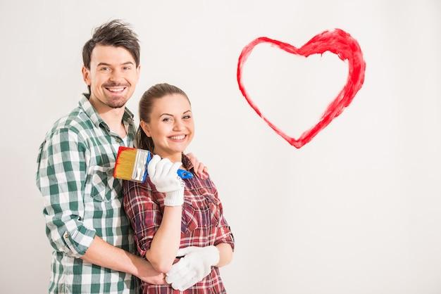 Jeune couple heureux peint un coeur sur le mur.