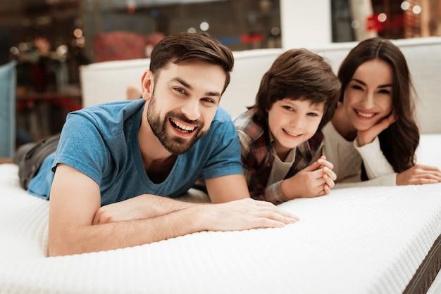 Jeune couple heureux et petit garçon sur lit en magasin