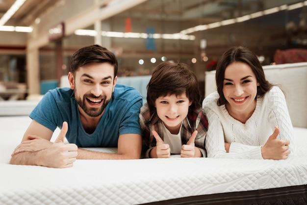 Jeune couple heureux et petite fille sur le lit en magasin