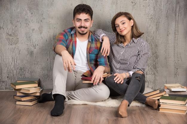 Jeune couple heureux posant à l'avant avec des livres à côté d'eux