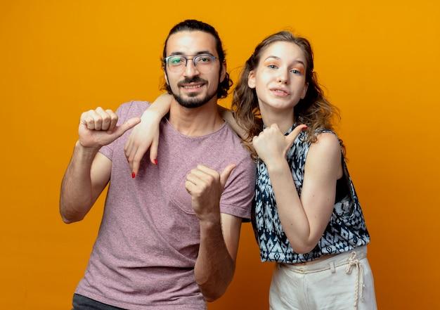 Jeune couple heureux et positif montrant les pouces vers le haut debout sur un mur orange