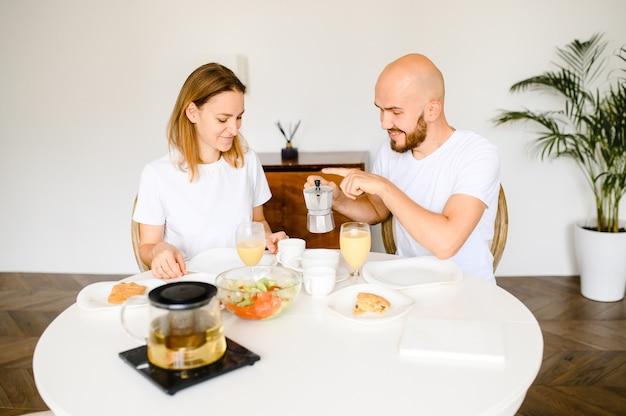 Jeune couple heureux prenant le petit déjeuner à la maison ensemble.